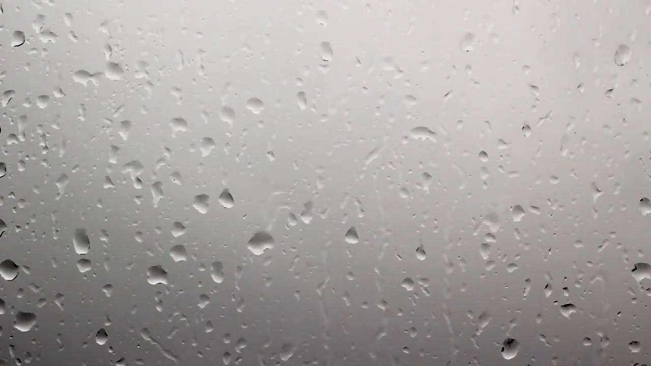 Raindrops falling on window with dark clouds in background stock video