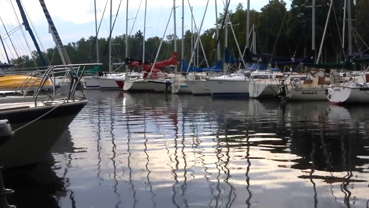 Sailboat On Reflecting clear Water at Port Stock Footage